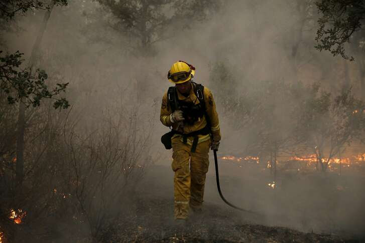Firefighter Tim Quickel walks out of the smokey underbrush near Middletown, California, on Sunday, Sept. 13, 2015.