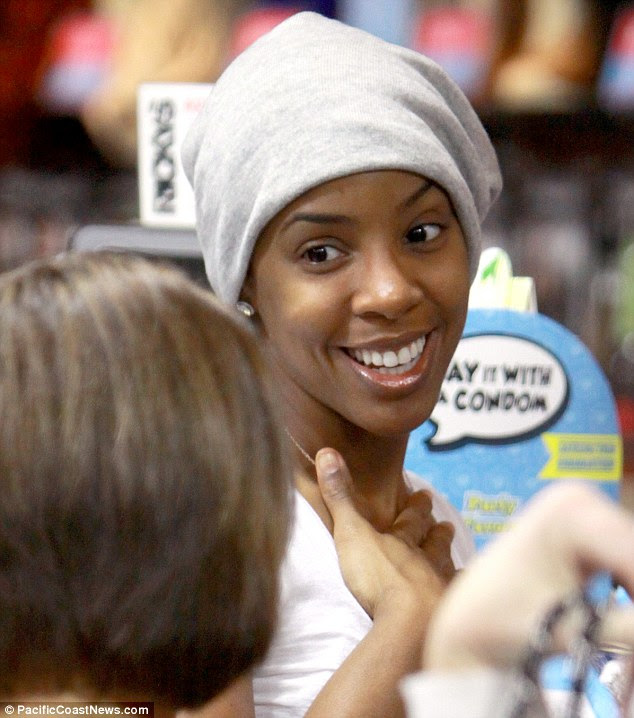 Winning smile: Kelly chatted warmly to another woman in the shop, perhaps to share some beauty tips