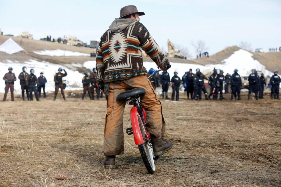 Un hombre observa el avance de las fuerzas de seguridad en el campamento contra el oleoducto Dakota Access.