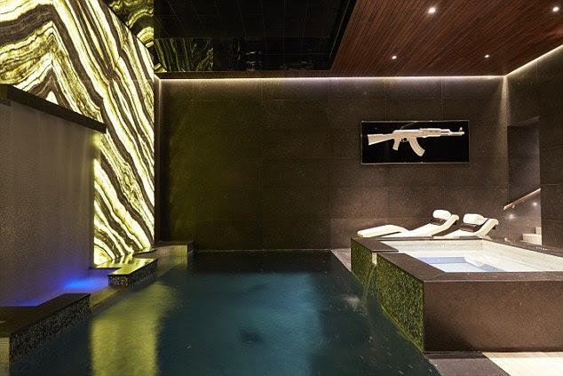 A família pode relaxar na piscina ou na banheira de hidromassagem ao lado dele.  Ónix retroiluminado anima a sala