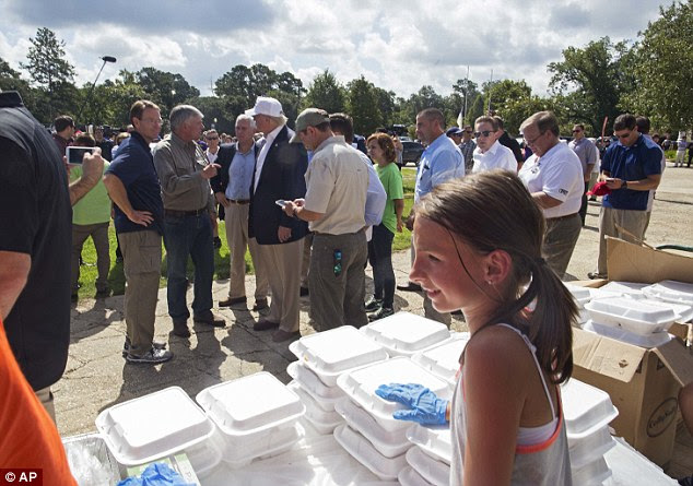 The Republican candidate and his running mate met with first responders who conducted rescues in the flooding - even as their own homes were damaged - and spoke with volunteers at a church that was helping nearby residents with cleanup