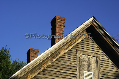 two brick chimneys on an old boarded-up house