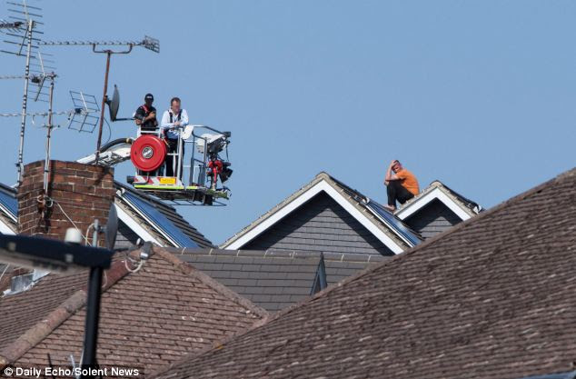Negotiators on a crane, left, desperately tried to coax Johnston, right, down from the roof of the house in Southampton, Hampshire, in baking 27C heat in July last year