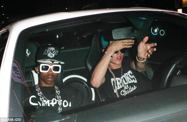 Frustrated: The popstar motions at paps to move as he tries to negotiate the car away from the club