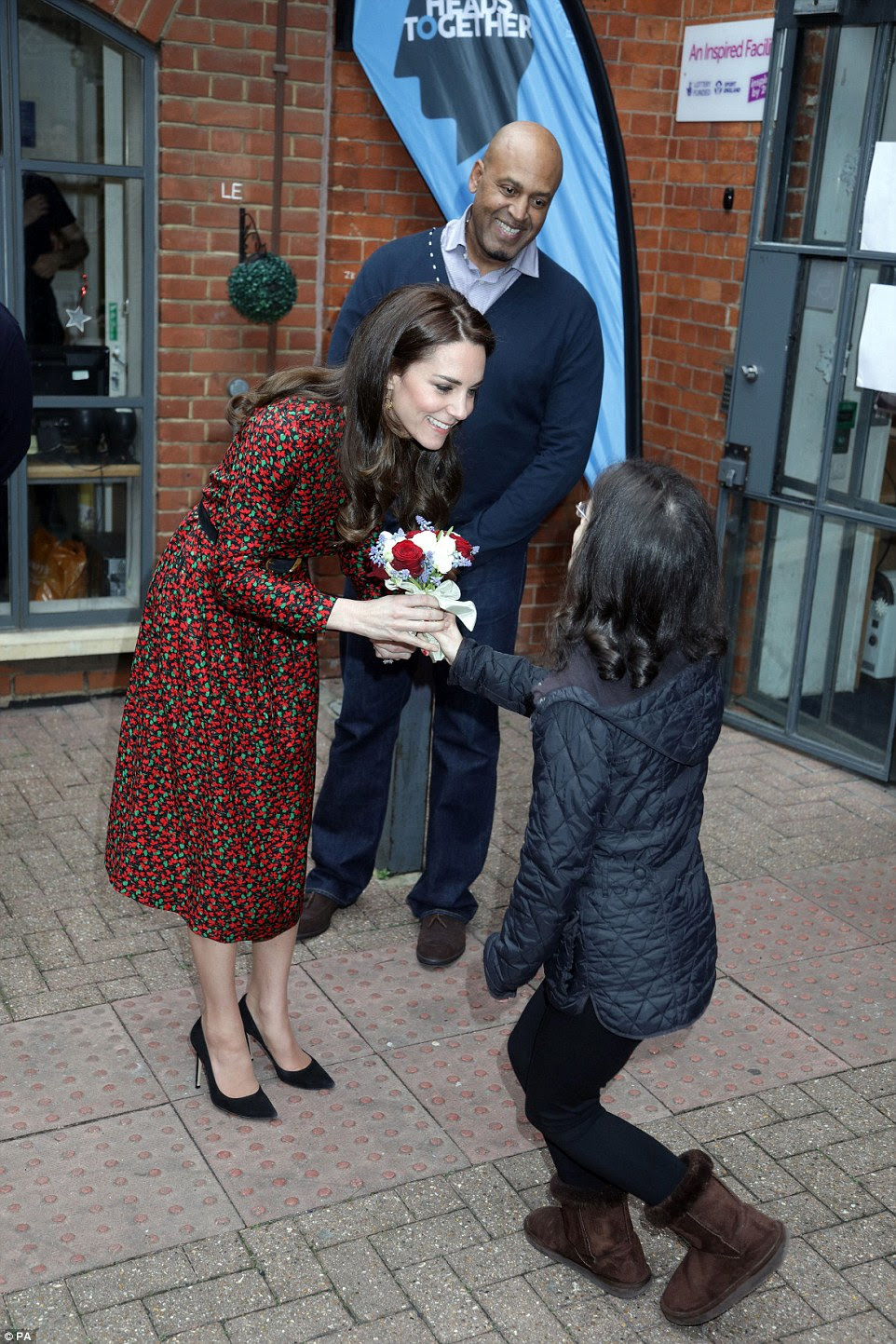 A young woman from The Harrow Club curtsies as she presents The Duchess with a small bunch of flowers