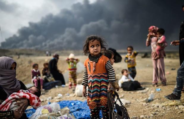 EI usa fumaça de incêndios para se proteger dos ataques aéreos (Foto: Bulent Kilic/AFP)