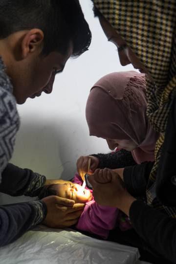 Rania, pediatra de Médicos del Mundo, atiende a una niña enferma ayudándose de la luz del móvil.