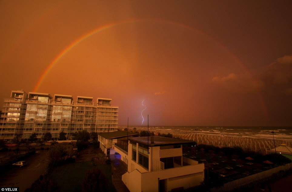 Miracles of nature: A rainbow arches across red clouds in Lido di Jesolo, Italy as a lightning bolt divides the sky in the distance