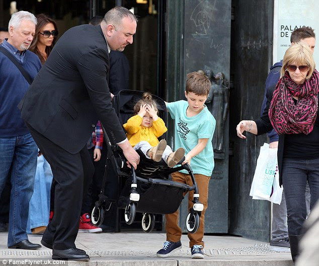 Helping hand: The youngest Beckham boy stepped in to help a shop doorman carry his sister's pushchair down the steps