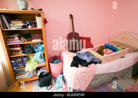 A teenager's messy bedroom with clothes, books and ...