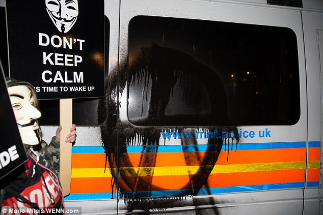 Graffiti was daubed on a police van, while a masked protester stood nearby waving a placard