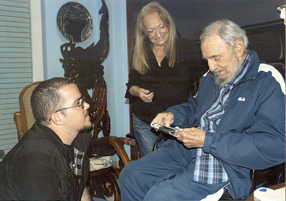 Former Cuban President Fidel Castro talks to President of Cuba's University Students Federation Randy Perdomo as Castro's wife Dalia looks on during a...