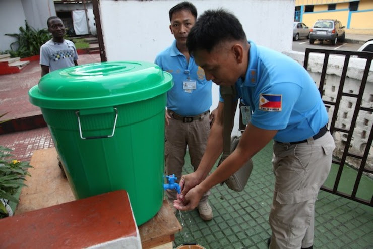 KEEPING CLEAN. United Nations peacekeepers from the Philippines wash their hands to avoid contact with the deadly Ebola virus before entering a service at the Providence Baptist Church in Monrovia, Liberia, 03 August 2014. Ahmed Jallanzo/EPA