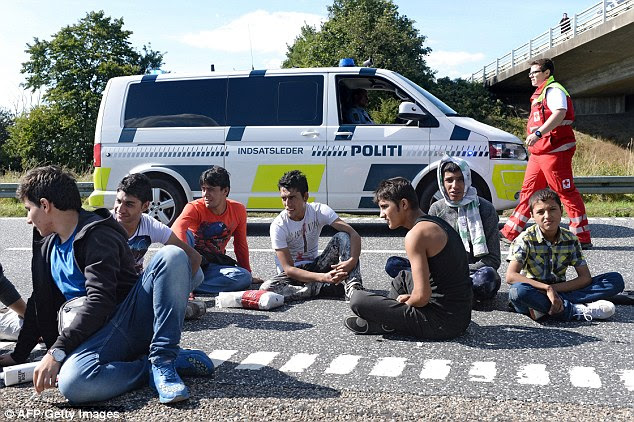 Critique: The government's proposal would bring asylum seekers (pictured near the German border in September) in line with unemployed Danes, who only get social benefits if they sell any valuables above £976