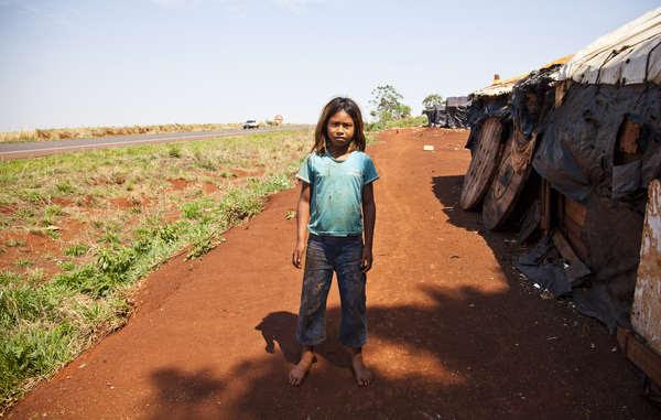 Fillette guarani devant son abri en bord de route - des champs sans fin ont remplacé la forêt luxuriante de son peuple. Beaucoup d'enfants se sont suicidé, la plus jeune n'avait que neuf ans.
