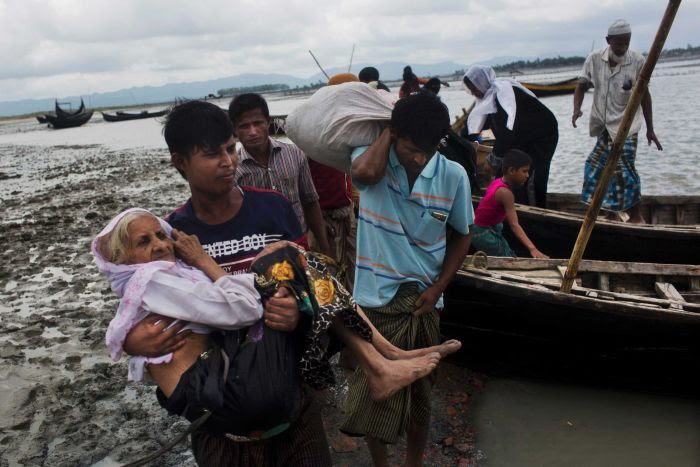 A Rohingya man carries an elderly woman from a boat