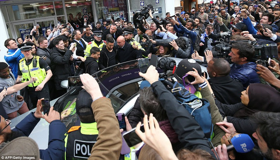 Leaving the restaurant: Leicester's Algerian midfielder Riyad Mahrez (centre) is helped to a car as he makes his way through crowds of fans
