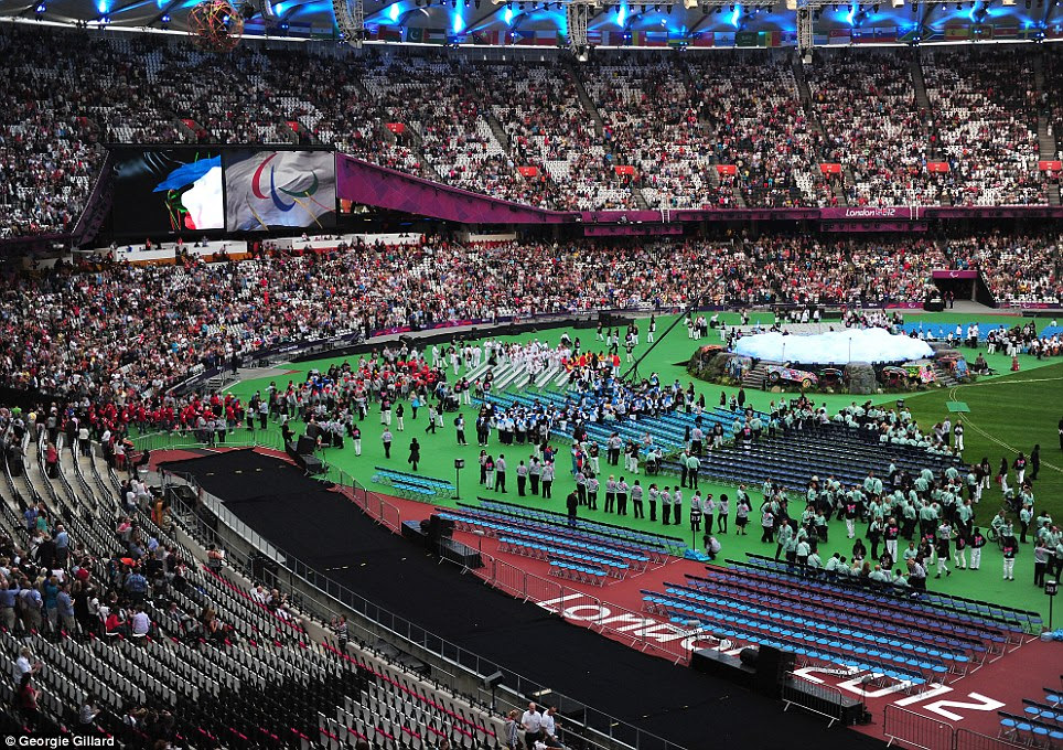 Finishing touches: A multitude of volunteers make the final preparations on the stage for the Closing Ceremony, which has been described as a 'Festival of flame'
