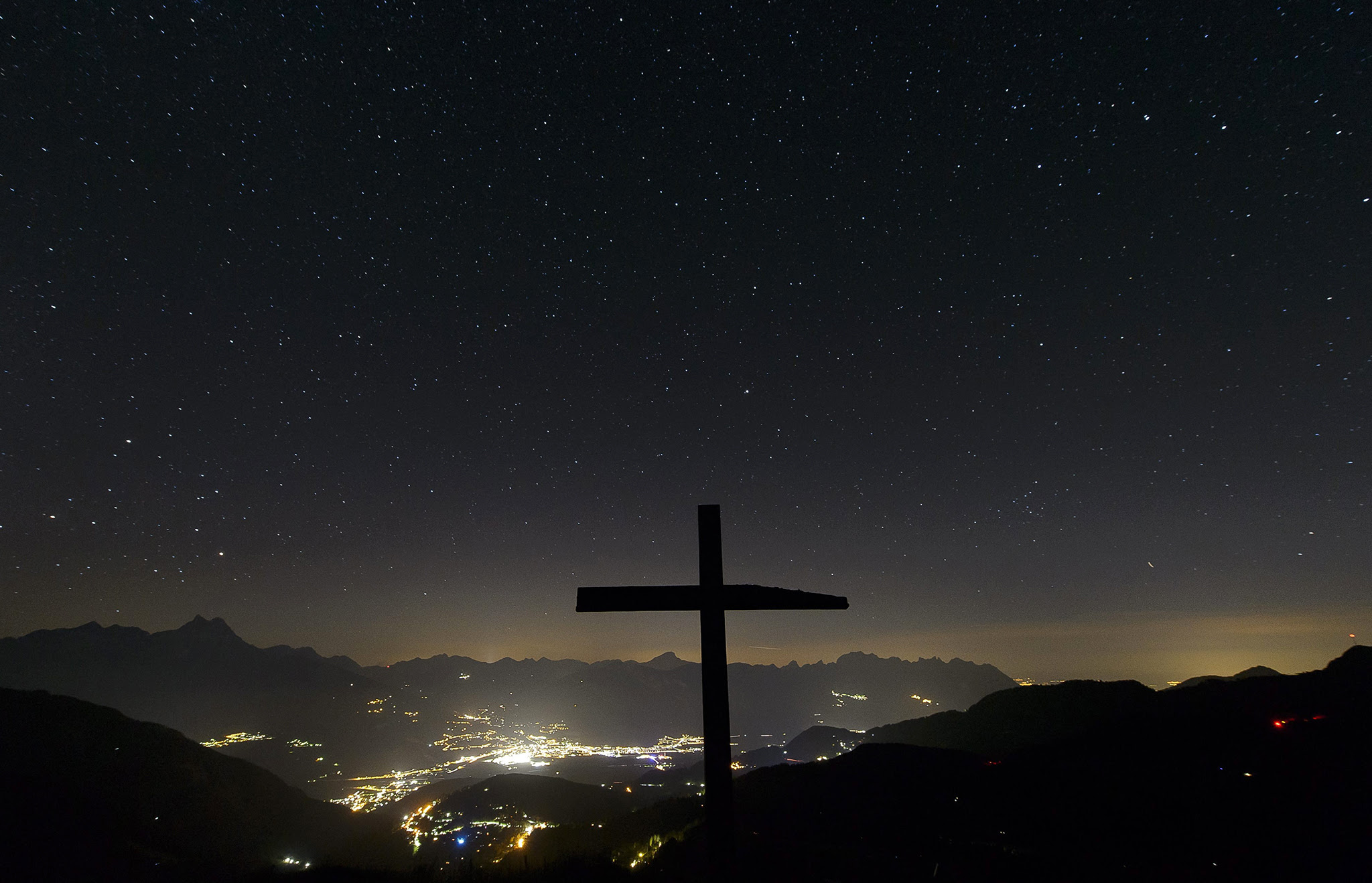 An image made available on 04 August 2016 shows a cross is pictured in front of the plain of Chablais at the summit of Croix des Chaux (2012m) above Gryon VD, western Switzerland, 03 August 2016.  EPA/ANTHONY ANEX