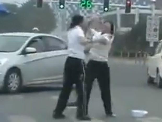 Policiais de trânsito foram flagradas trocando socos no meio da rua, e precisaram ser apartadas por outra oficial (Foto: YouTube/Reprodução/Carey Lee)