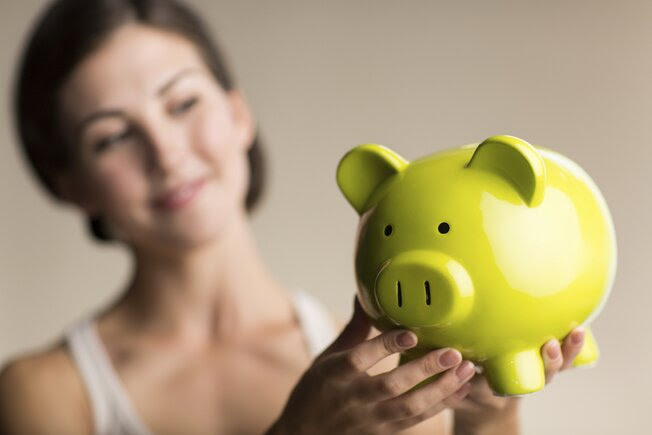 A young woman holding a piggy bank.