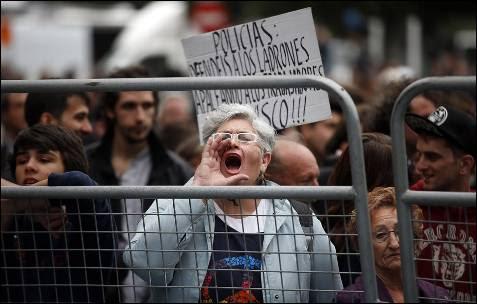 Una mujer protesta frente a las vallas que impedían el acceso al Congreso de los Diputados.