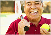 Man holding a tennis racquet and smiling.