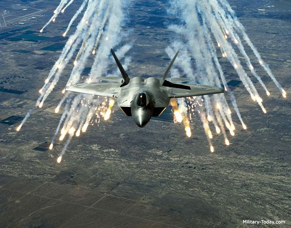 An F-22 Raptor fires flares while in flight.