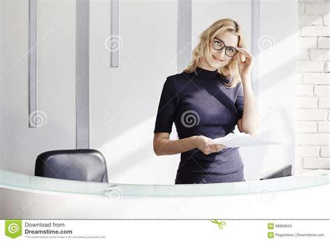 beautiful blonde friendly woman   reception desk