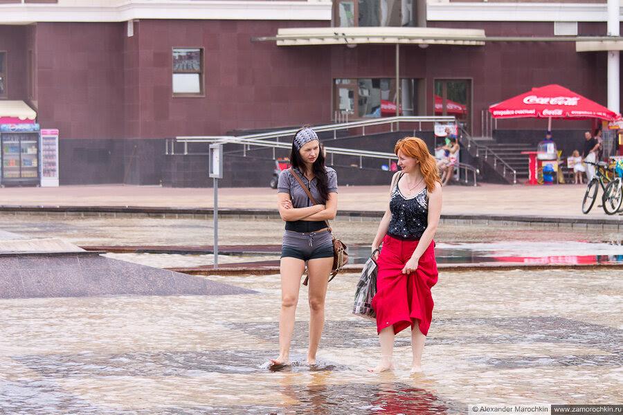 Девушки гуляют босиком в фонтане