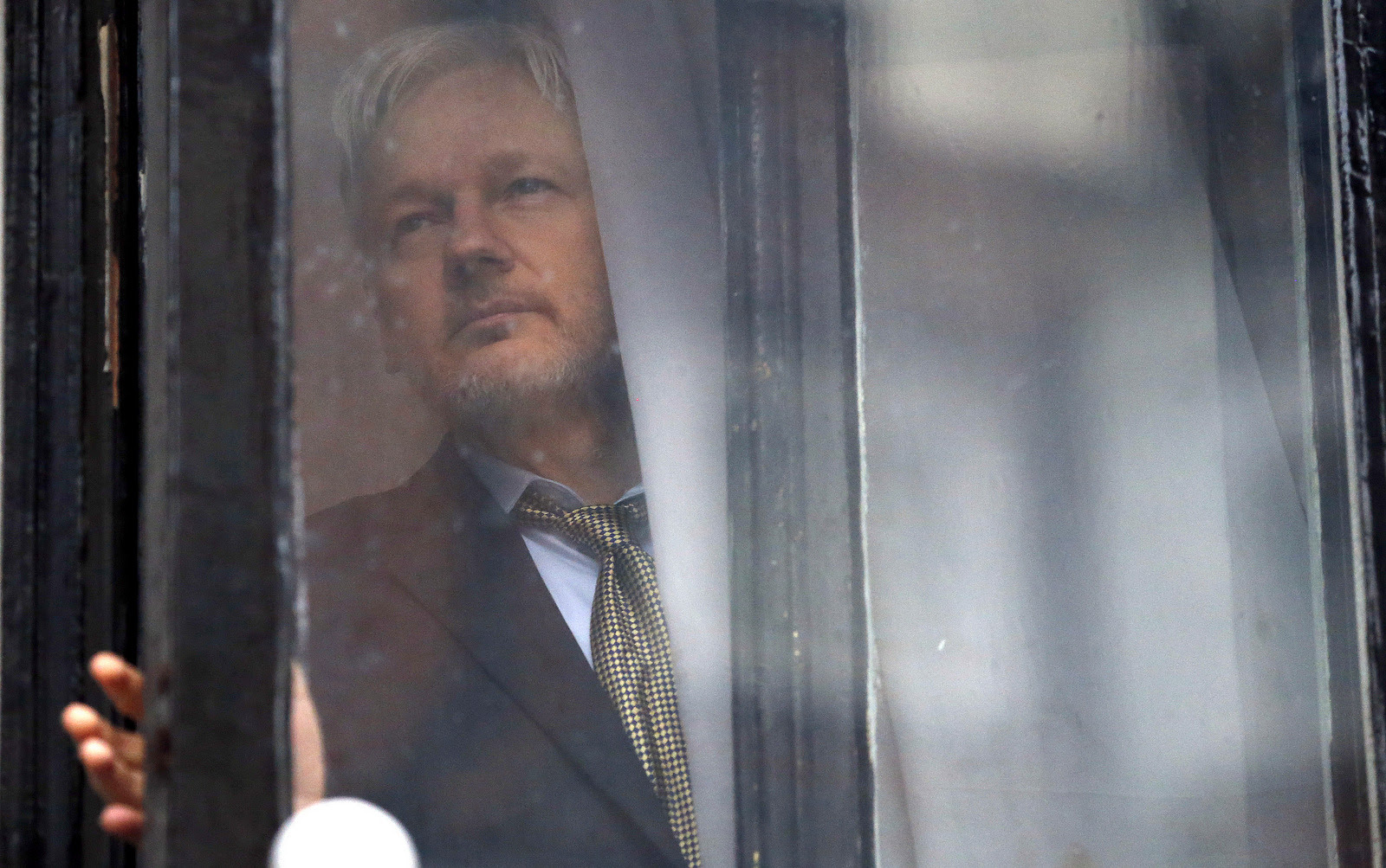 WikiLeaks founder Julian Assange walks onto the balcony of the Ecuadorean Embassy to addresses waiting supporters and media in London, Friday, Feb. 5, 2016. (AP/Frank Augstein)