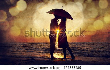 Couple kissing under umbrella at the beach in sunset. Photo in old image style. - stock photo