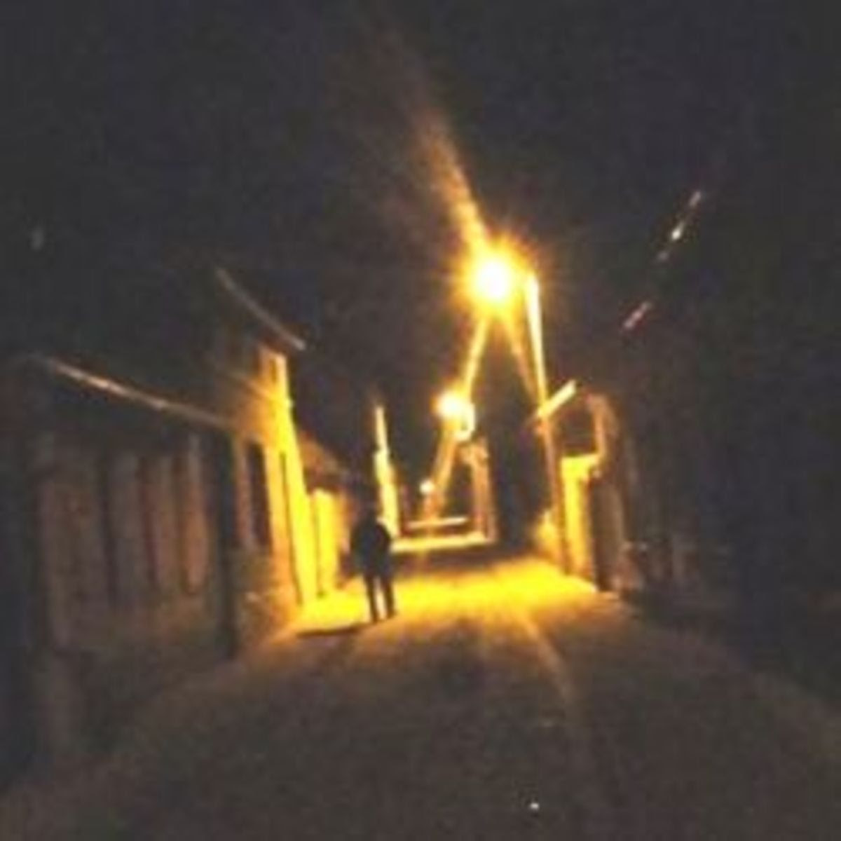 A tilted view of a person walking down a poorly-lit street at night.