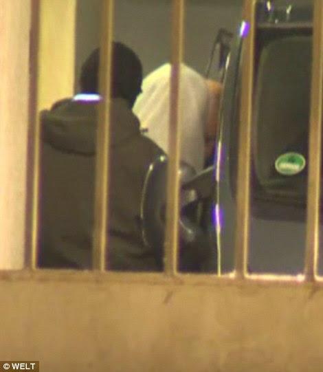 Primeira foto: The Masked 23-year-old nomeado como Naved B, que entraram no país sob um nome falso na véspera do Ano Novo de 2015, é mostrado aqui sendo empacotados em uma van da polícia depois de sua prisão