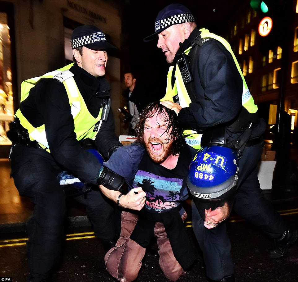 A man is detained by two police officers on Regent Street in London during the Million Mask March bonfire night protest