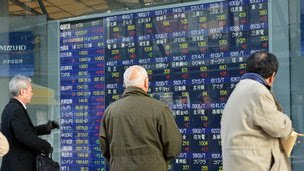 Investors looking at a stock market board in Tokyo