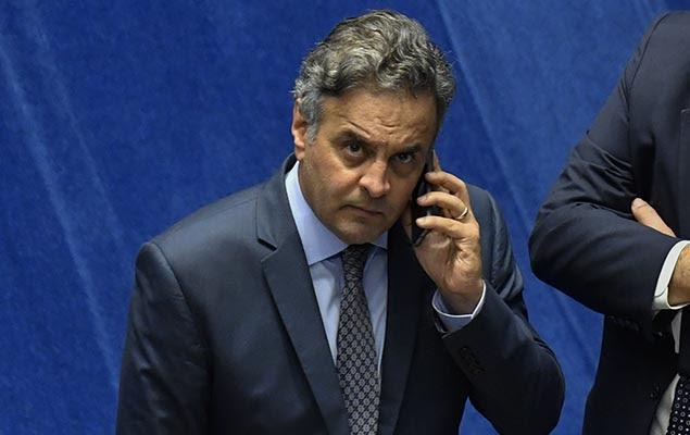 Senador Aécio Neves (PSDB) fala ao telefone durante sessão no Senado, em Brasília, na noite desta quarta