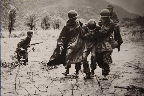 Kapaun, right, and a doctor help an exhausted soldier in Korea.