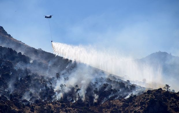 A helicopter drops water over a hillside at Lake Isabella, California on June 24, 2016.