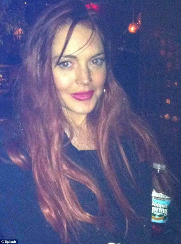 Smilingr: Lindsay Lohan clutches a bottle of Poland Spring water at Avenue club just before her arrest