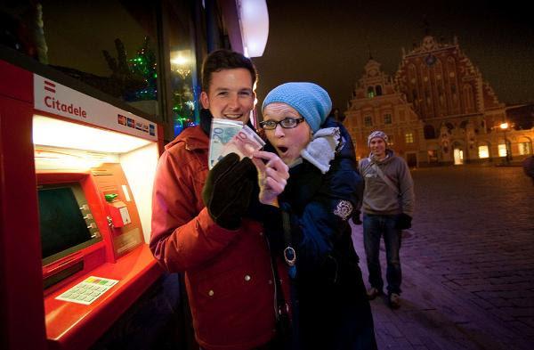 Dos jóvenes letones enseñan sus billetes de euro recién sacados de un cajero en Riga el 1 de enero de 2014 ©BELGA/AFP/A.LIEPINS