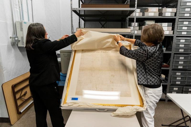 From left, Deputy Attorney General Karen Blum and state Archivist Sarah Koonts reveal North Carolina's copy of the Bill of Rights.