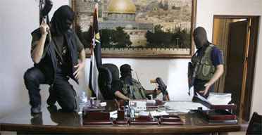 Palestinian militants from Hamas stand at the desk of Palestinian President Mahmoud Abbas inside Abbas' personal office after it was taken over by Hamas in fighting in Gaza City. Photograph: Hatem Moussa/AP.