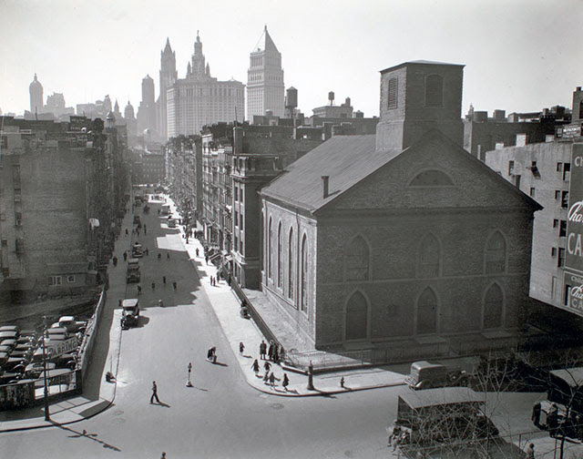 General view, looking southwest to Manhattan from Manhattan Bridge, Manhattan. Looking down Monroe Street toward Municipal building and financial district; children play on corner near church, parking lot, left.