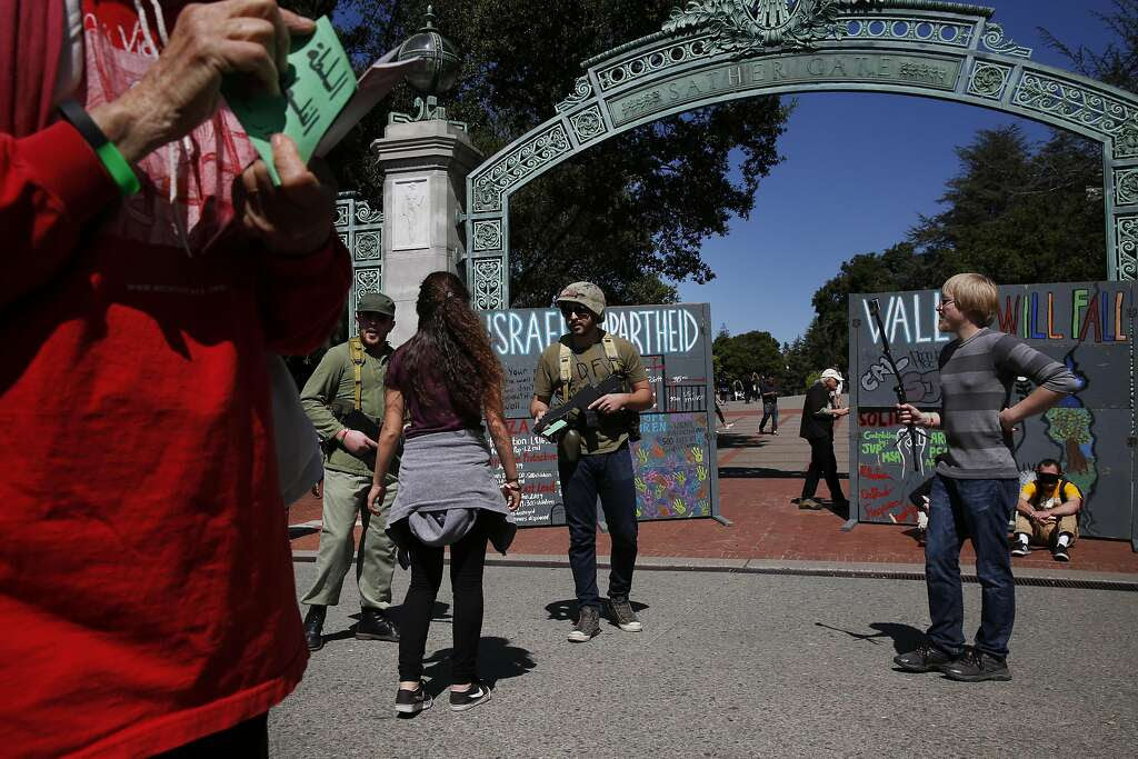 David McCleary (right) takes video as Palestinians' supporters role-play during a mock Israeli checkpoint demonstration near Sather Gate at UC Berkeley. Photo: Leah Millis, The Chronicle