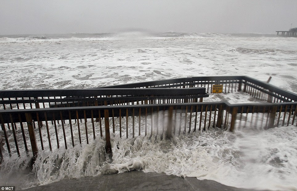 Waves crash next to the Atlantic City Boardwalk, already advancing past the beach, as wind speeds strengthen to 90mph