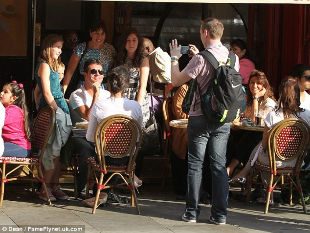 Cowell is all smiles as a passer-by grabs a photo of the music mogul while pregnant Ms. Silverman looks on