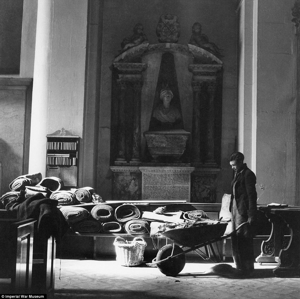 Blitz spirit: A workman clears debris from the floor of st Mary-le-Bow after its first bombing. The church was completed destroyed in 1942.