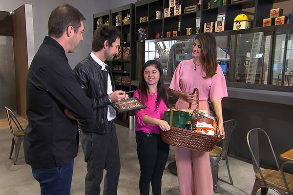 A participante Thais segura uma cesta de chocolates da Cacau Show. Está rodeada por Alexandre Costa, Arlindo Grund e Isabella Fiorentino