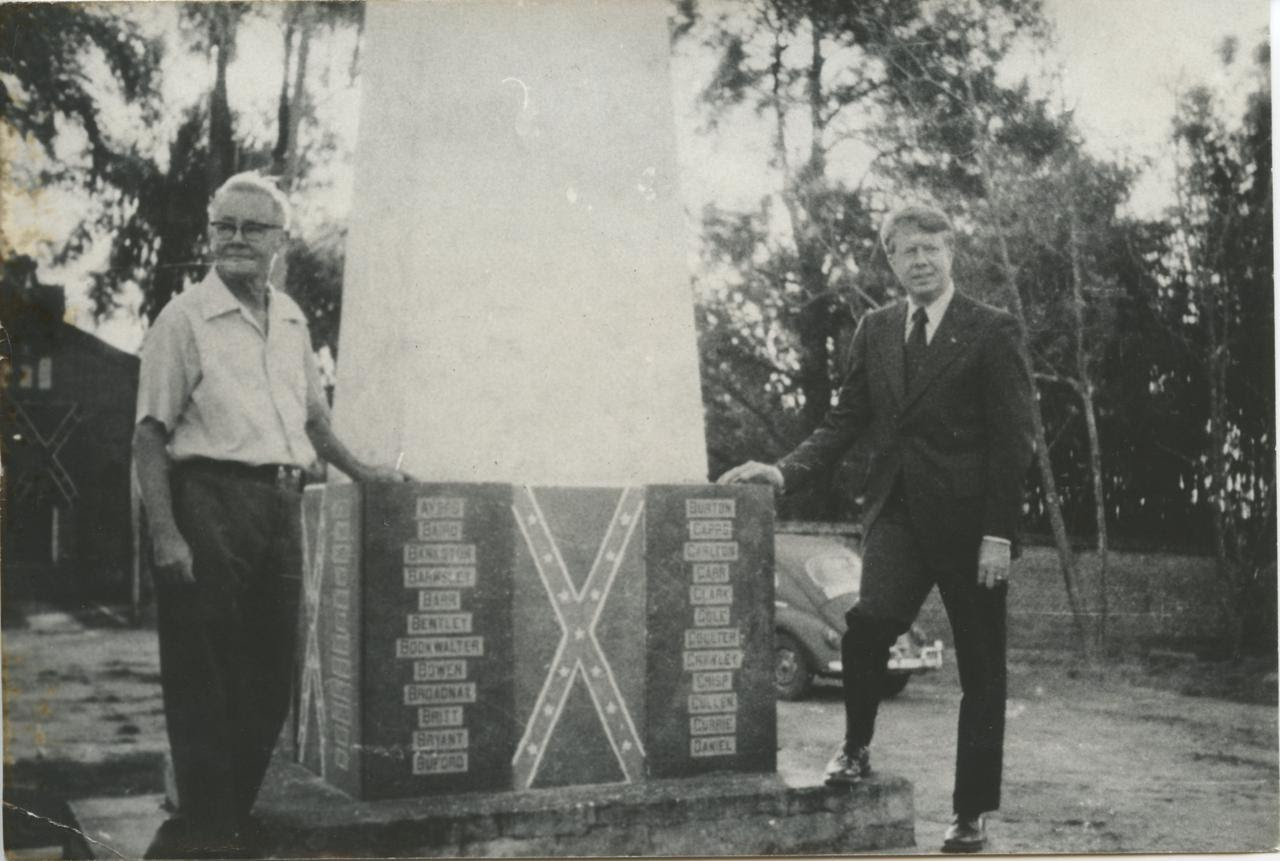 Americana resident Jim Jones stands with then-Georgia Governor Jimmy Carter alongside a commemorative monument at the Americana cemetery. Carter made the visit in 1972.  Notice the Confederate insignia and names of the original ninety-four settlers of Americana etched in the based on the monument. (Photographer unknown)
